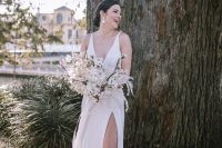 a modern glam bride wearing a plain A-line wedding dress with no sleeves, a deep neckline and a front slit, nude shoes and statement earrings