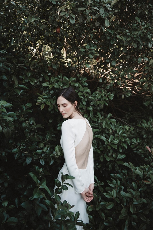 a modern plain fitting wedding dress with a triangle cutout back and long sleeves is an ultimate solution for a modern bride