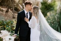 a modern plain flare wedding dress with a square cut back and neckline, with puff sleeves, a train and a long veil with blooms is wow