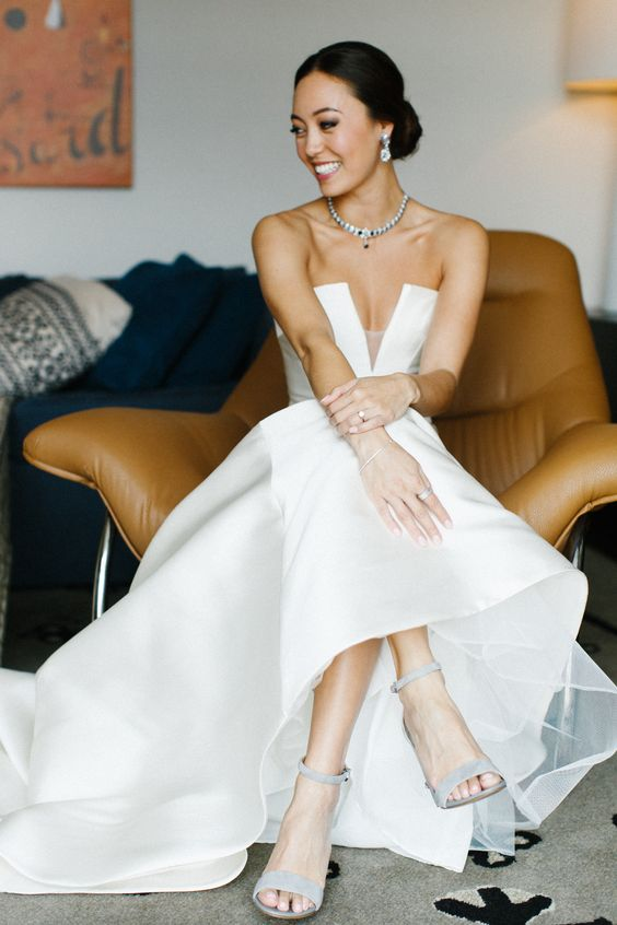 a modern strapless wedding ballgown with a geometric and deep neckline and a train, grey ankle strap shoes and statement accessories