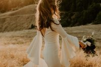 a modern yet extremely romantic mermaid wedding dress with a cutout back, bell sleeves and a train is a lovely idea for a modern bride