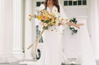a plain white wedding dress with a covered plunging neckline, wide bell sleeves and a train plus a retro veil for a frehs look