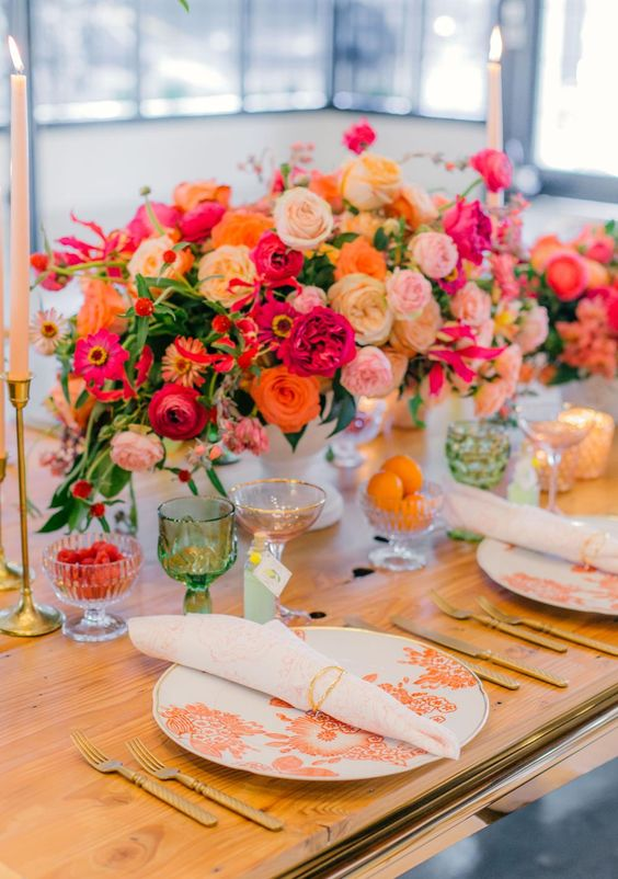 a pretty and bold bridal shower tablescape with a bold floral centerpiece, hot pink, orange and pale pink blooms, florla print plates and colored glasses