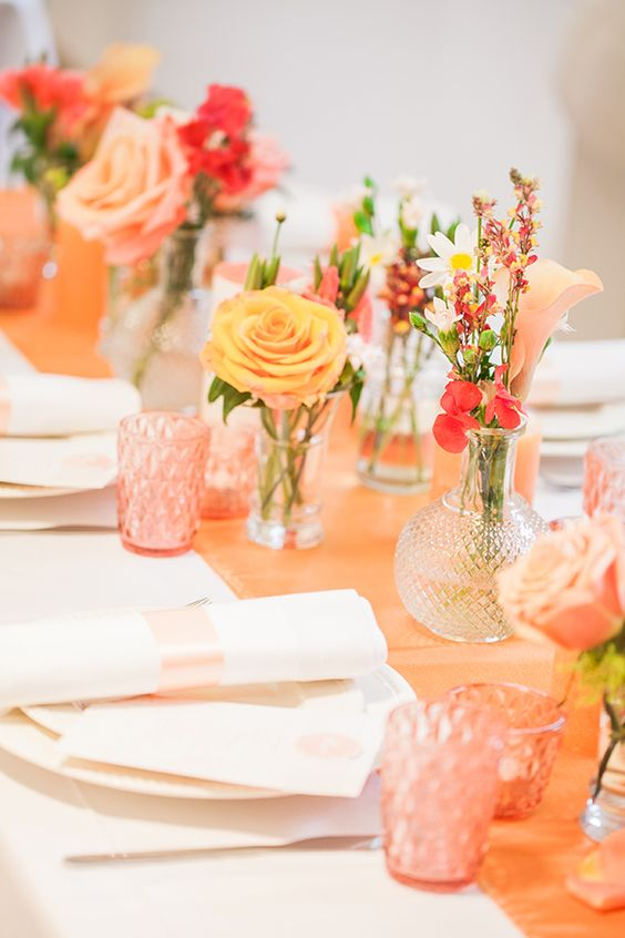 a pretty and colorful bridal shower tablescape with an orange table runner, bold blooms, colored glasses and white plates and napkins is cool