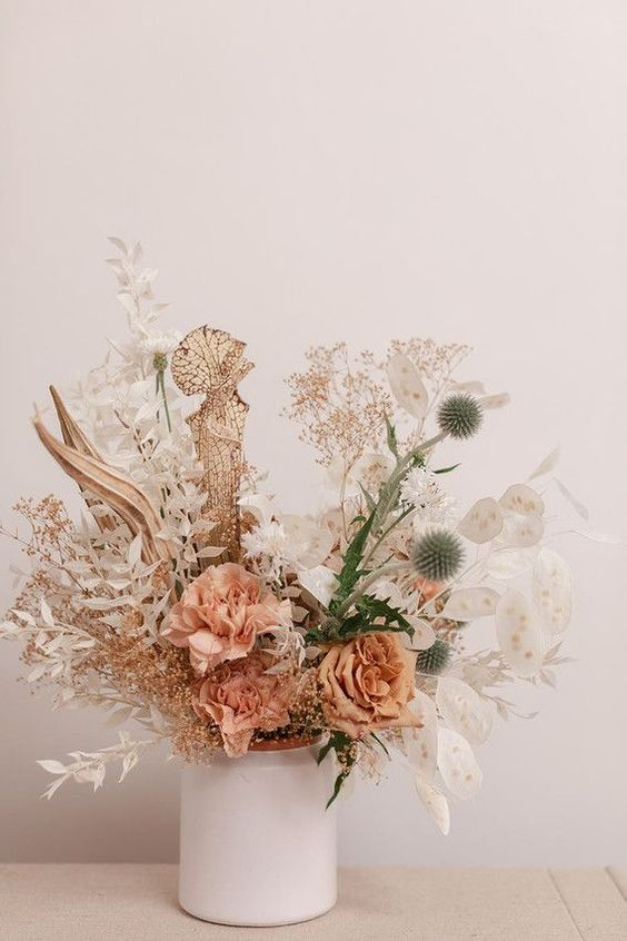 a pretty dried and fresh flower centerpiece with lunaria, dried and white spray painted leaves, with allium, rust and peachy roses is cool