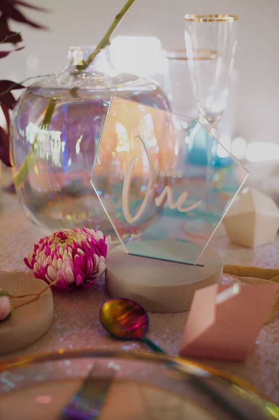 a pretty iridescent wedding place setting with a holographic escort card, a teapot, pink stones and an iridescent place setting