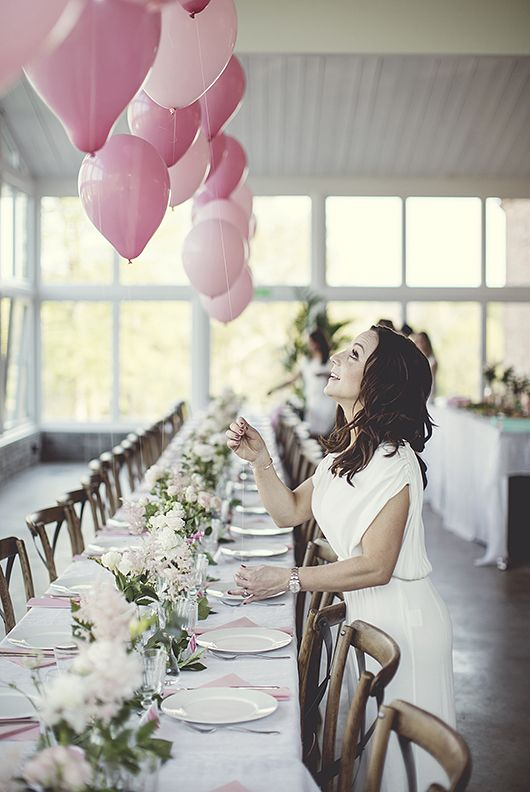 a pretty modern wedding tablescape with pink balloons and blush and white blooms and greenery and pink napkins
