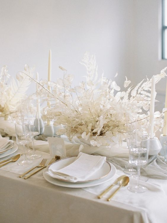 a really ethereal dried leaf wedding centerpiece with lunaria is ideal for an all-white wedding tablescape and it looks chic and elegant