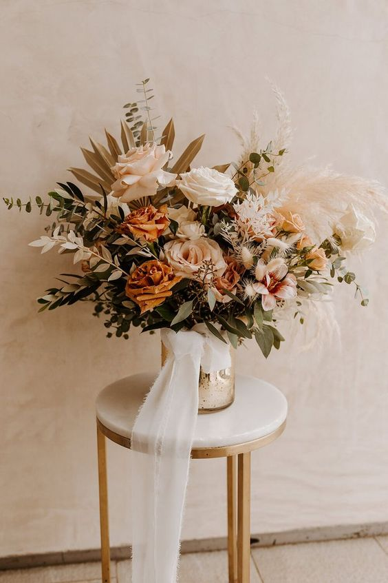a refined neutral fall boho wedding centerpiece of blush, rust, white blooms, lots of various greenery, pampas grass and dried fronds