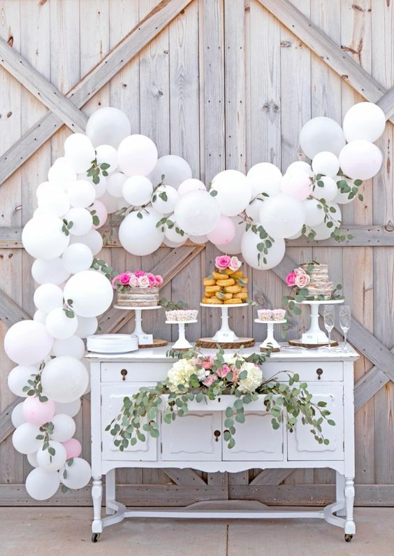 a refined vintage sweets table of a white dresser, with greenery, white blooms and a white balloon garland with greenery is gorgeous