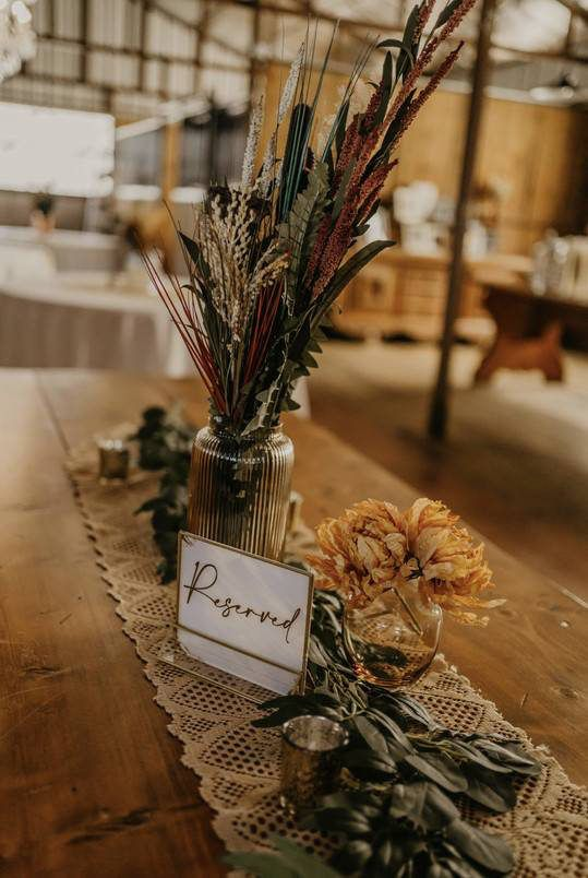 a simple and relaxed fall boho wedding centerpiece of a glass jar with dried flasses, leaves, greenery on the table and dried blooms, a macrame runner