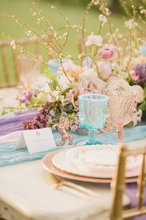 a stylish iridescent wedding tablescape with pink, purple and turquoisetable runners, pink plates, pink and blue glasses and a lovely pastel wedding centerpiece