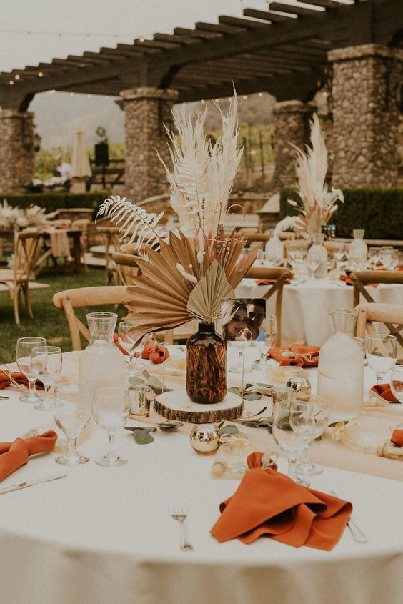 a summer or fall wedding centerpiece of an apothecary bottle, dried fronds, leaves and a wood slice plus greenery is a lovely idea