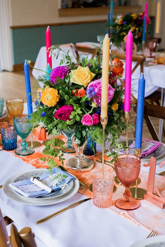 a super bright bridal shower tablescape with a peachy runner, colorful candles, pink napkins and super bright glasses plus bold and colorful blooms and greenery