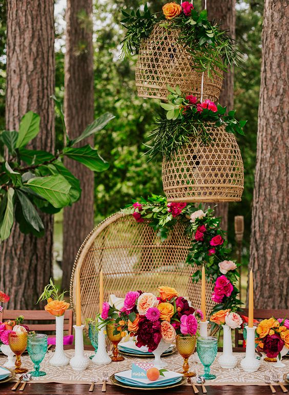 a super colorful bridal shower tablescape with a printed runner, colored glasses, bold bloom centerpieces, pink blooms and greenery to decorate the chairs and pendant lamps