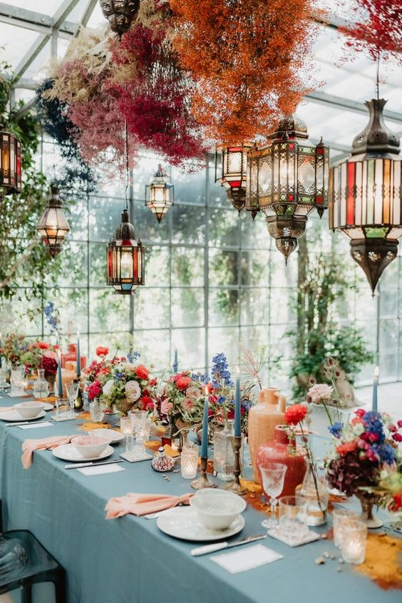 a super colorful bridal shower tablescape with spray painted dried blooms and Moroccan lanterns, bold blooms, colorful candles and pink napkins