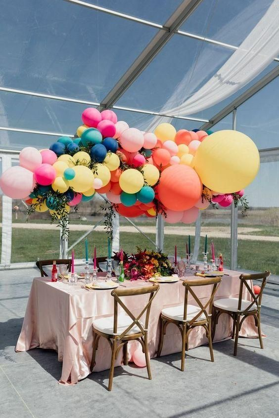 a super colorful wedding tablescape with bold candles and blooms, with an oversized colorful balloon installation over the table