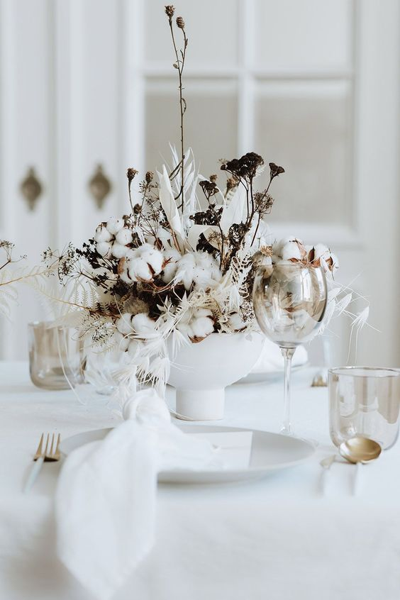 a textural and creative winter wedding centerpiece of cotton, dried blooms and whitewashed leaves and grasses is a bold idea