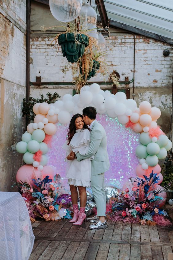 a unique wedding backdrop with holographic sequins, bold spray painted blooms and pastel and white balloons is a masterpiece