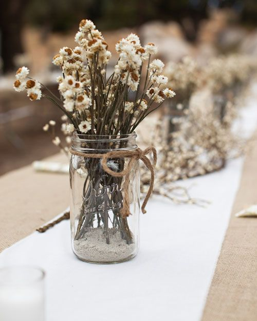 a very simple boho wedding centerpiece of dried daisies in a jar is a lovely and easy to DIY idea for a wildflower wedding