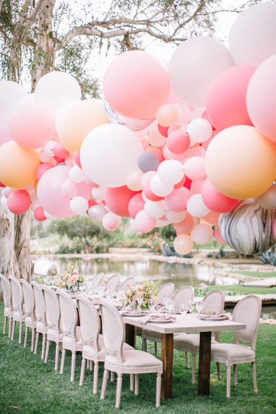a vintage and refined wedding tablescape with a whitewashed table and chairs, pink blooms, a bright oversized balloon garland over it for a playful touch