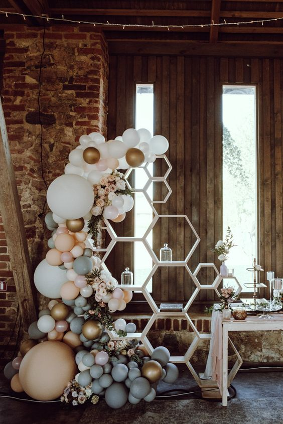 a wedding dessert bar with a hexagon shelf and white, gold, peachy and grey balloons plus white blooms is a lovely idea