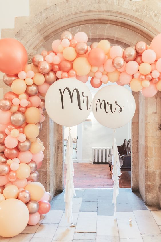 a wedding entrance styled with pink, pearly and blush balloons and white balloons with tassels is a very cool idea