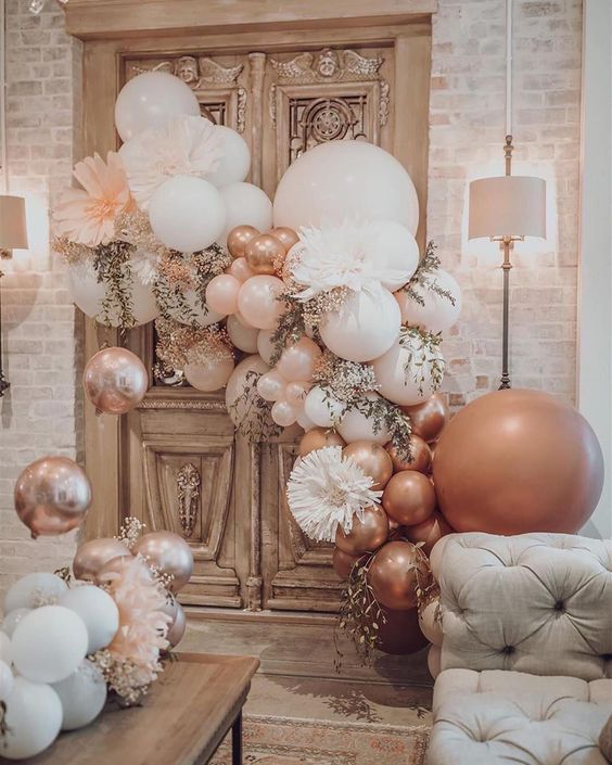 a wedding lounge styled with blush and pink balloons, pink blooms and greenery is a very chic and cheerful idea to rock