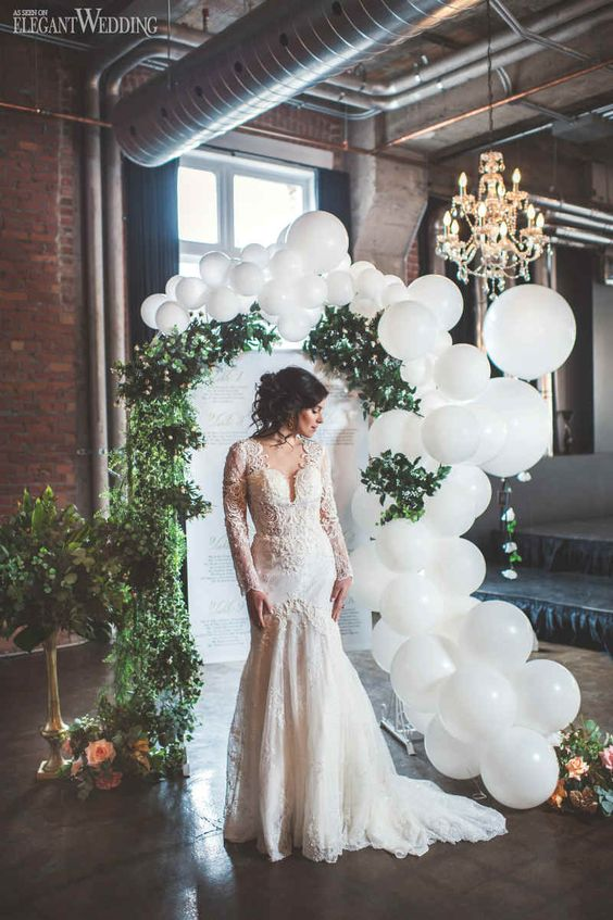 a wedding sign styled with greenery, pastel blooms and white balloons is a very pretty and cool idea for a modern wedding