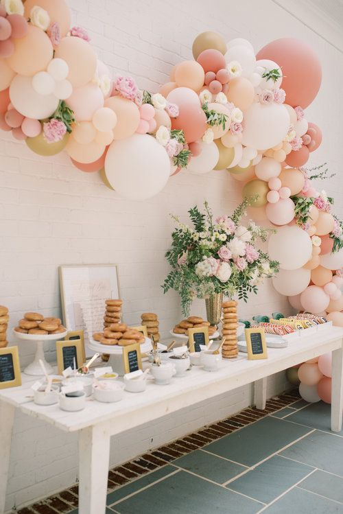 a wedding sweets table with white and pastel blooms plus greenery, pink, white, coral and gold balloons and blooms over it is amazing