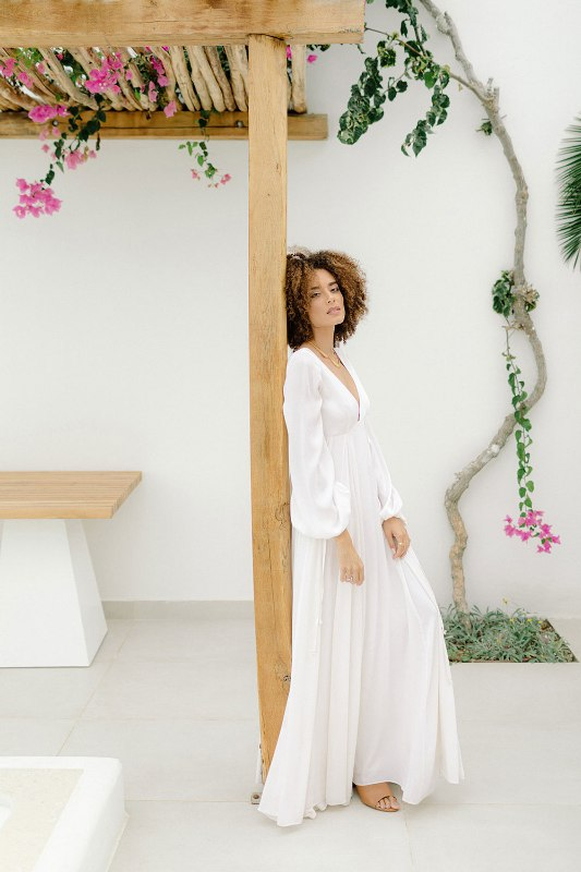 an A-line plain wedding dress, with a plunging neckline and long puff sleeves paired with nude mules for a modern tropical wedding