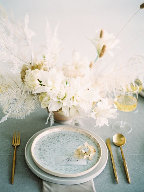 an airy wedding centerpiece of white and neutral blooms, bunny tails, whitewashed leaves is a beautiful idea for a spring wedding