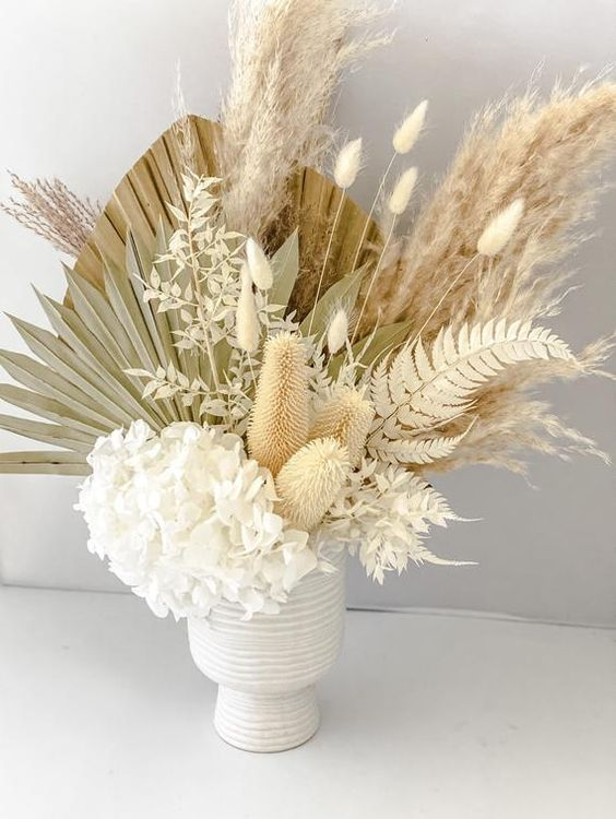 an airy wedding centerpiece of white hydrangeas, bunny tails, dried fronds and leaves is a textural and very creative idea