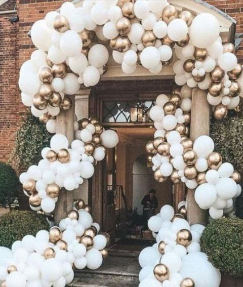 an entrance in a wedding venue all covered with white and gold balloons looks gogeous, statement-like and no worse than if it was covered with blooms
