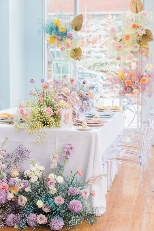 an iridescent wedding reception space with bold blooms and baby's breath, with statement fronds and pastel place settings