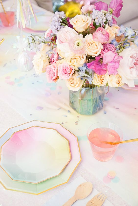an iridescent wedding table setting with bold chargers, plates and blooms, with an colorful iridescent tablecloth