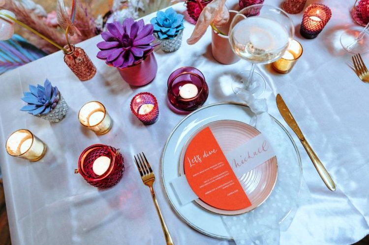 an iridescent wedding table setting with pink, blue and other touches, with candles, a blush plate and a colorful menu is wow
