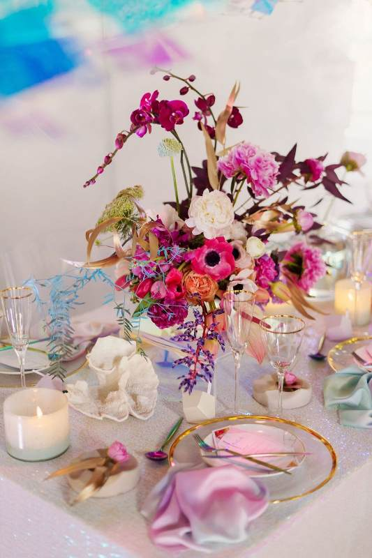 an iridescent wedding tablescape with a clear charger, blush dip dyed napkins, bold blooms and iridescent leaves and foliage, white candles