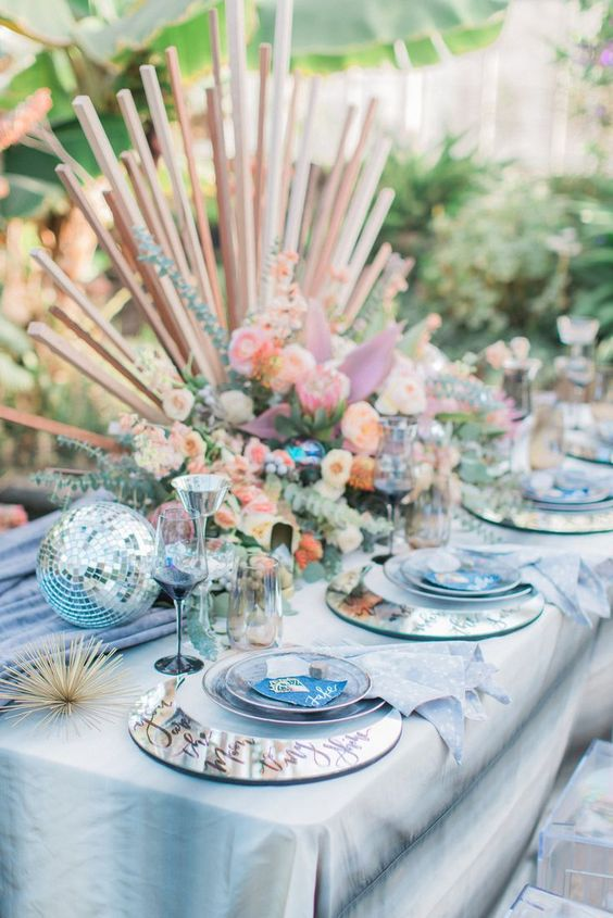 an iridescent wedding tablescape with a dip dye tablecloth, a blue runner, pastel and iridescent blooms and slabs, mirror chargers and disco balls