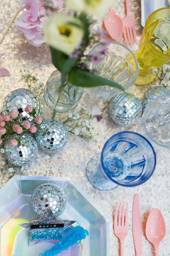an iridescent wedding tablescape with disco balls, blue and yellow glasses, pink cutlery, iridescent chargers is wow