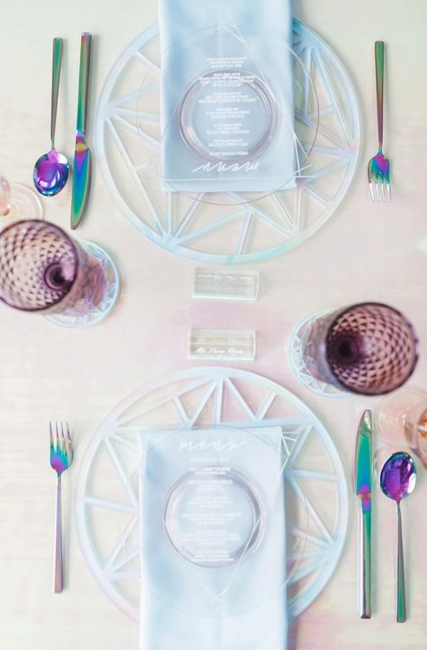 an iridescent wedding tablescape with iridescent wedding chargers, blue napkins, iridescent cutlery and purple glasses