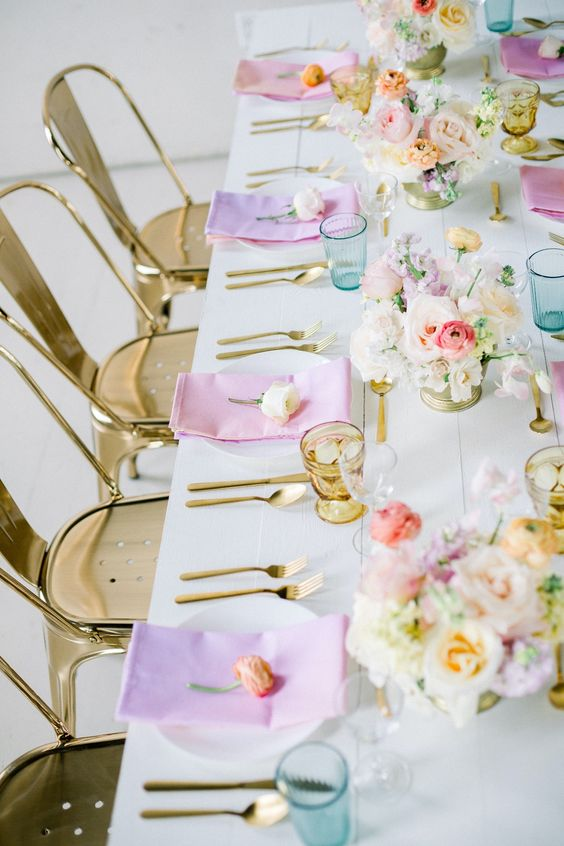 an iridescent wedding tablescape with pink and lilac napkins, pink, blush, lilac and peachy blooms, gold glasses and cutlery