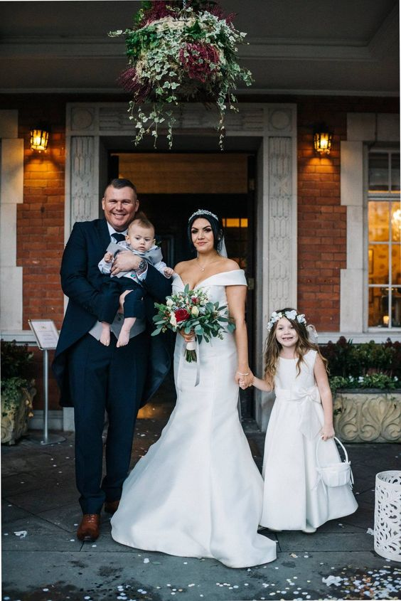 an off the shoulder mermaid wedding dress with a plunging neckline, a rhinestone headpiece and a veil for a glam bridal look