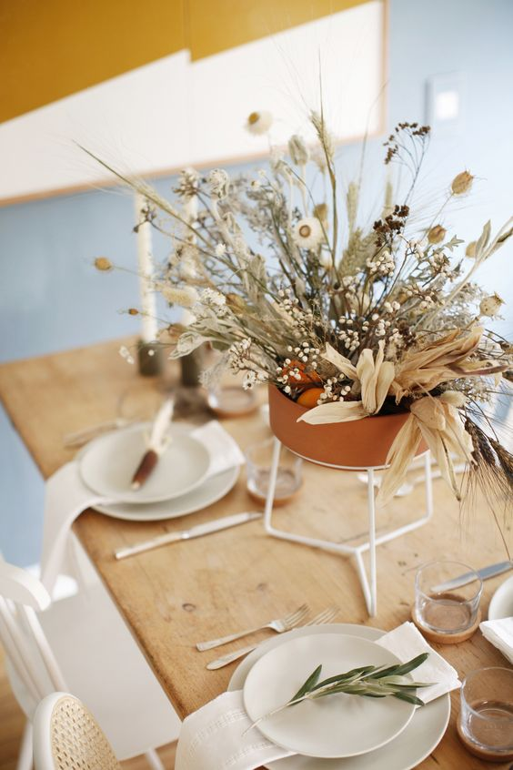 an organic wedding centerpiece of a terracotta vase, with dried blooms, berries, grasses and whitewashed leaves is a chic idea