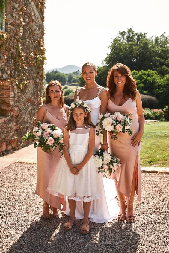 blush slip midi bridesmaid dresses with V-necklines and asymmetrical skirts for a glam spring or summer wedding