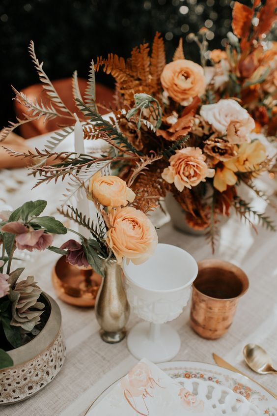 bold boho fall wedding centerpieces of orange, blush and rust blooms, greenery, bold foliage and candles around are cool