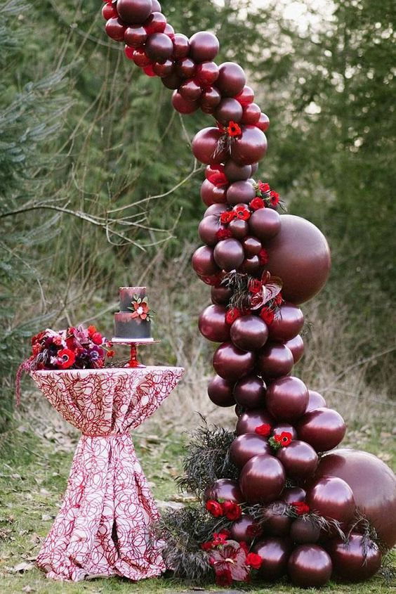 burgundy balloons, red blooms and greenery for a bold wedding decoration over the dessert table is a very statement idea