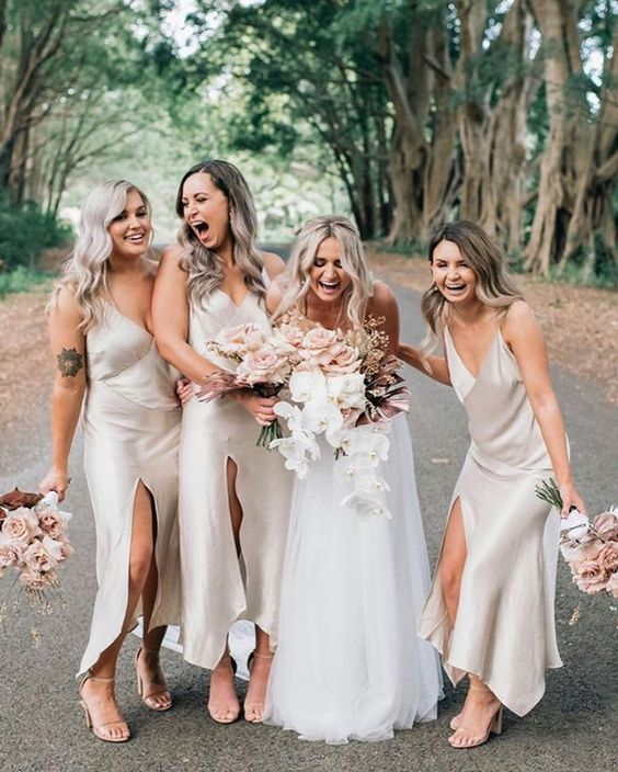 comfy and cool neutral slip midi bridesmaid dresses with front slits and V-necklines plus nude heels for a spring or summer wedding