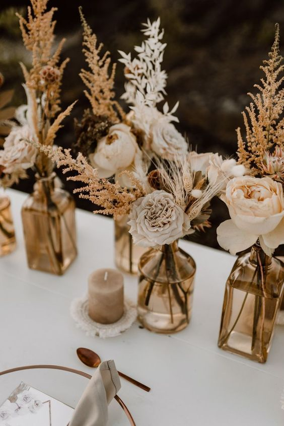 cool boho fall wedding centerpiece of dried blooms, branches, leaves, grasses and peachy and light pink blooms, with colored vases and a neutral candle