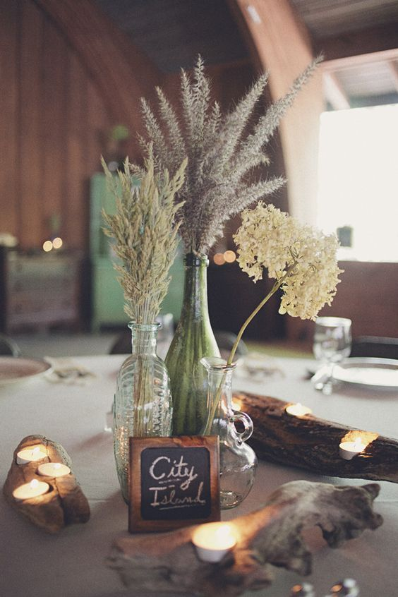 dried flower and grass arrangements in vintage bottles, with a chalkboard sign and some small candles around for a rustic wedding centerpiece